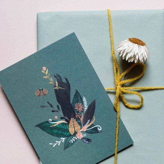 Postkarte mit einer Hand, die aus Blütenblättern kommt
